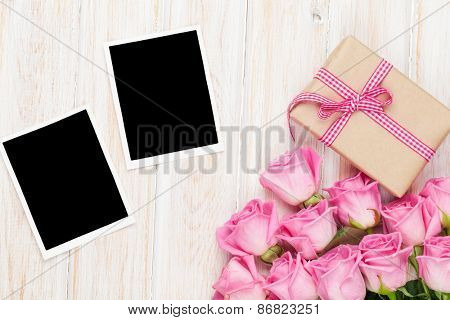 Pink roses and valentines day gift box and two blank photo frames over wooden table. Top view with copy space