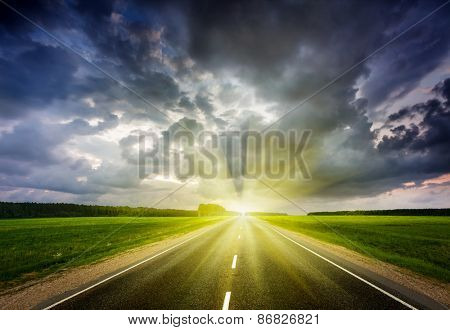Travel concept background - road and stormy dramatic sky on sunset