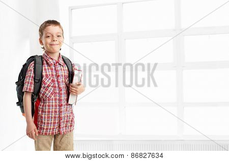 Schoolboy with backpack at school. Child at classroom
