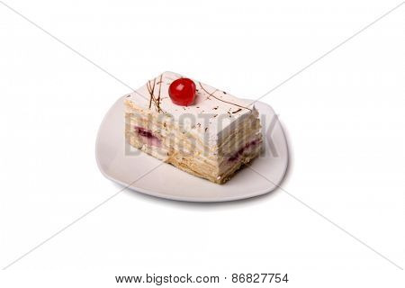 Creamy cake with cherry on white plate, isolated on white background with clipping path