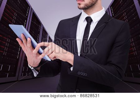 Mid section of a businessman using digital tablet pc against server hallway