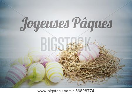 joyeuses paques against easter eggs with straw