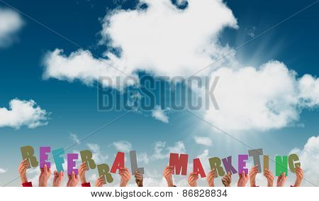 Hands showing referral marketing against blue sky