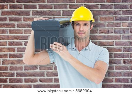 Confident worker carrying tool box on shoulder against red brick wall