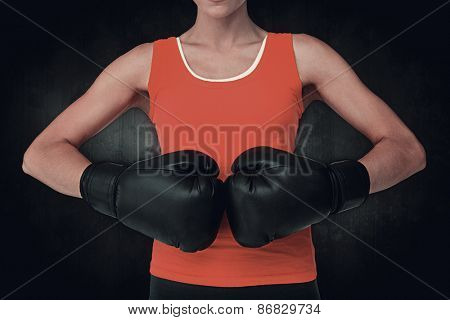Close-up mid section of a determined female boxer against dark background