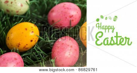 Happy Easter greeting against many little easter eggs in the grass