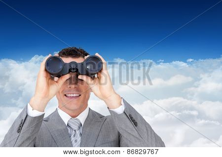 Businessman holding binoculars against bright blue sky over clouds