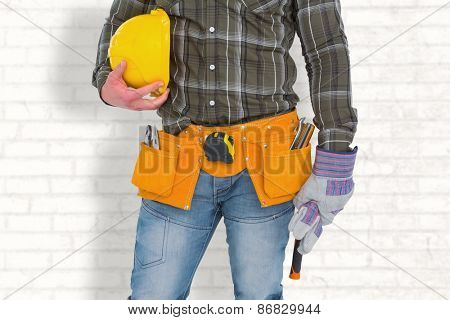 Manual worker wearing tool belt while holding gloves and helmet against white wall
