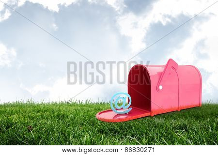 Red email post box against field and sky