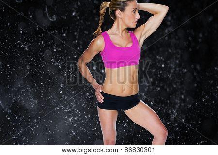 Female bodybuilder posing in pink sports bra against black background