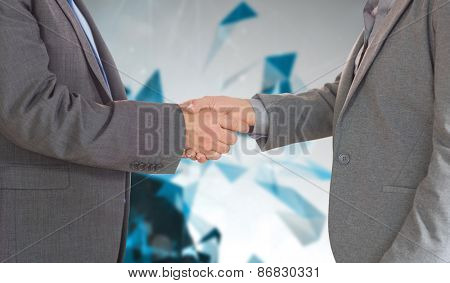 Close up on two businesspeople shaking hands against angular design
