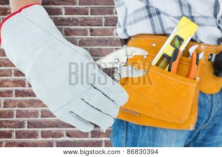 Technician using pliers over white background against red brick wall