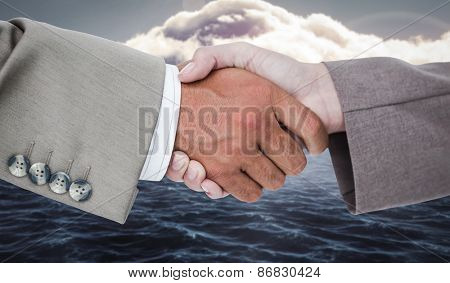 Side view of business peoples hands shaking against calm sea with lighthouse