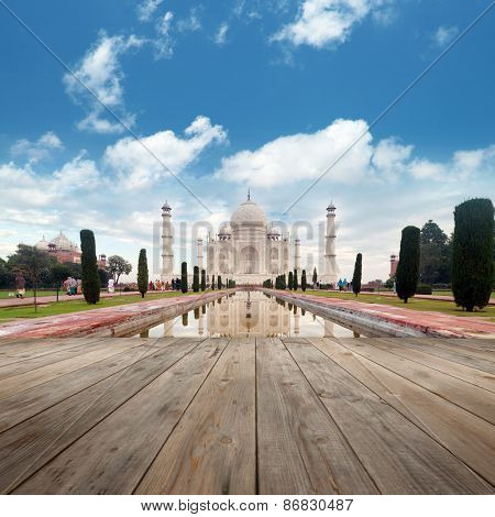 A perspective view from wooden balcony to Taj Mahal mausoleum with reflection in water.