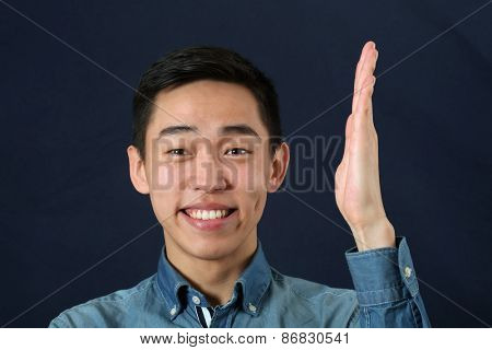 Smiling young Asian man holding his hand upright and looking at camera