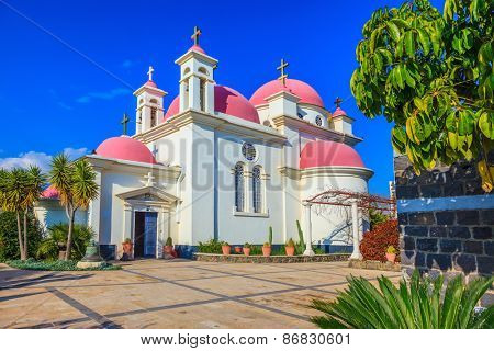 Pink domes and golden crosses crowned with snow-white church building. Greek church of the Cathedral of the twelve apostles