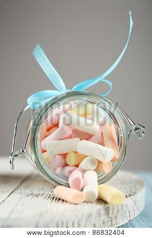 Sweet candies on wooden table on gray background