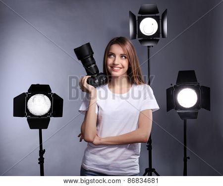 Young female photographer taking photos on grey background