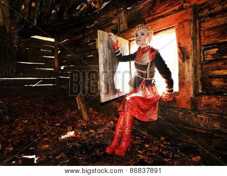 Beautiful blonde woman in old wooden house