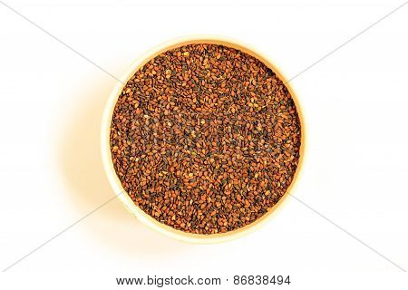 dark coloured variety of sesame seeds kept in a bowl on a plain background