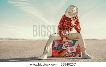 Tourist Sitting On A Suitcase
