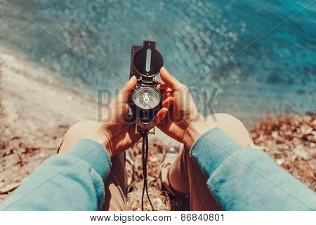 Traveler Holding A Compass On Coastline