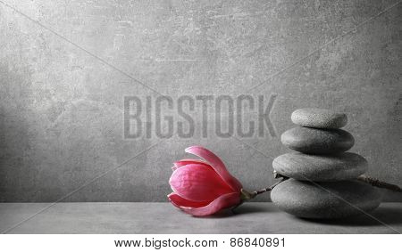 Zen stones and magnolia flower on vintage background