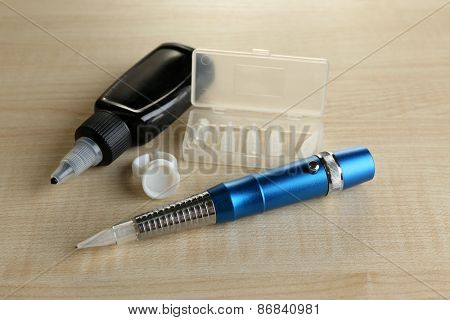 Machine for permanent make up (tattoo) and bottle with black ink, on wooden background