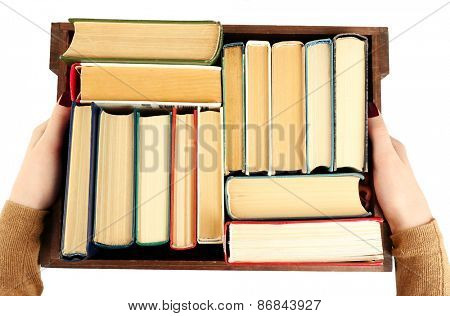 Books in wooden box in female hands, top view