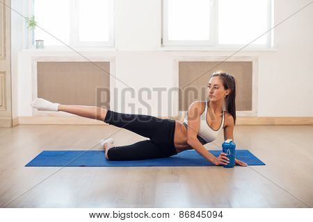 Young dark-haired athletic active sporty slim woman doing yoga exercise the gym or home stretching h