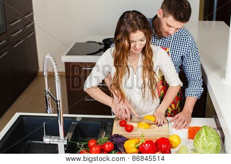 Young couple preparing a salad diet vegetable in the kitchen at home.