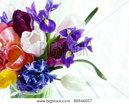Beautiful bouquet of spring flowers in glass vase on curtain background