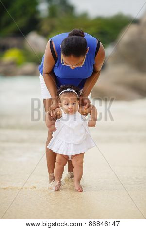 Mother and little daughter on the beach near the ocean.