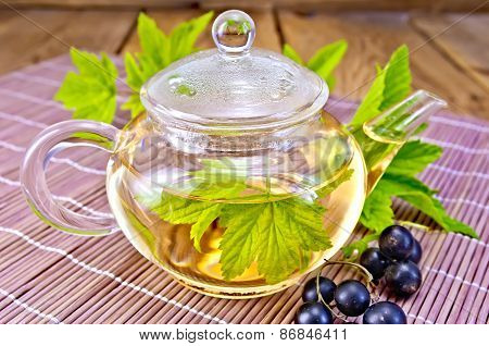 Tea with black currants in glass teapot on board