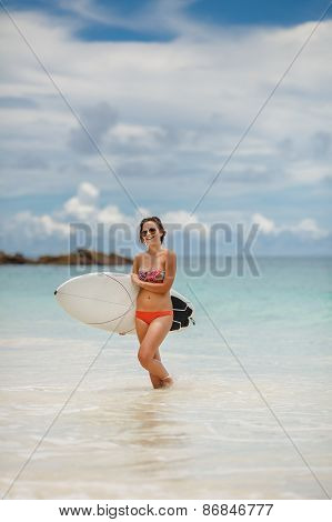 A beautiful surfer girl at the beach holding up her surfboard