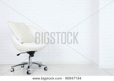 Modern chair with pillow on white brick wall background