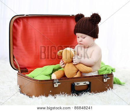Cute baby boy in funny cap sitting  in big suitcase on carpet, on light background