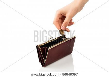 an empty wallet and a hand which holds a coin in front of white background