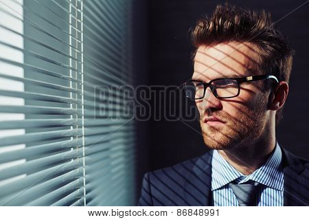 Confident young businessman in eyeglasses looking through venetian blinds