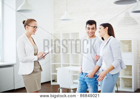 Confident female realtor consulting young couple