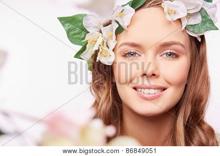 Joyful girl in floral wreath looking at camera with toothy smile