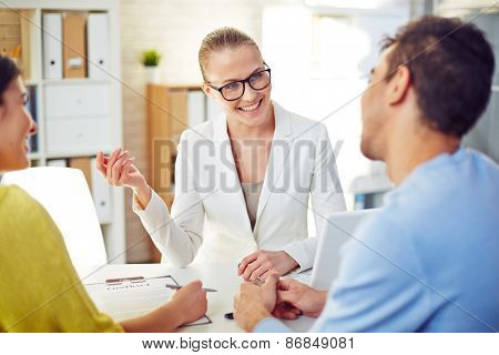 Female realtor explaining young couple terms of contract