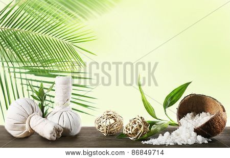 Spa compress balls, sea salt and green leaves on light background