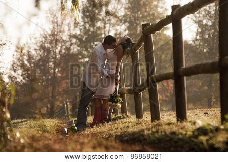Happy couple outdoors flirting against picket fence
