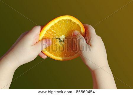 Orange Slice In Children's Hands