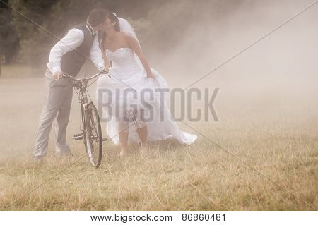 Happy newly wed couple outdoors in field with vintage bicycle