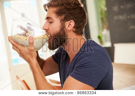 Hungry Young Man Eating Breakfast From Glass Bowl