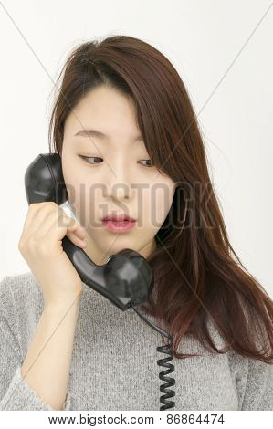 Depressed asian woman talking by telephone