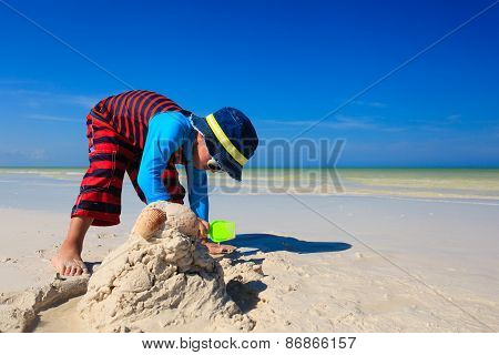 little boy digging sand on tropical beach