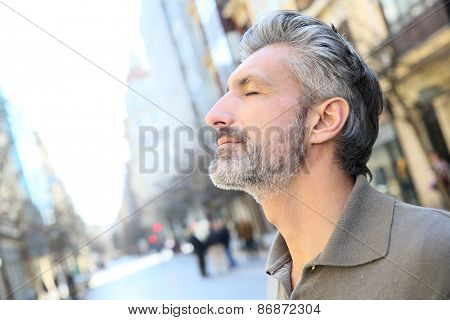 Portrait of serene mature man in town